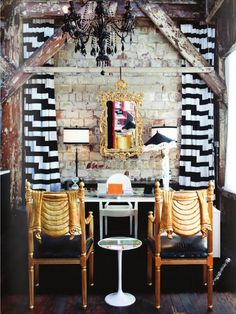 Gosh, so many surprising things happening in this room: those black & white drapes, the tan chairs, the seriously distressed wood beams, and that gaudy gold mirror! Eclectic!