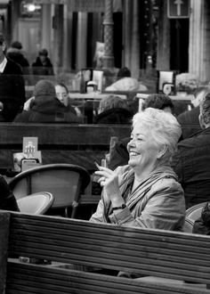 A Smoke and A Laugh - Woman enjoying conversation at a cafe in Brussels, Belgium