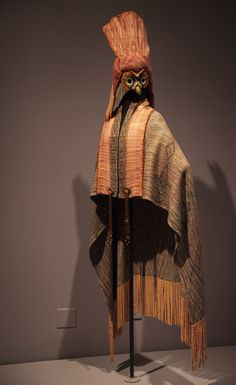 Margaret Roach Wheller, Chickasaw Born 1943, workd in Joplin, Missouri The Messenger (The Owl) cape and headpiece, Mahotan Collection, 2014 For Mahota Handwovens Cape: silk-wool yarn Headpiece: silk-wool yarn, metal, silver, glass beads, and peacock feathers On loan from Portland Art Museum, museum purchase with funds provided by an anonymous donor This ensemble turns two-dimensional handwoven fabric into a three-dimensional soft sculpture. In the Native worldview of the Southeast, birds…