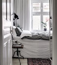 Small bedroom done right. Light makes it work. Wall sconce save the space of big end tables and lamps.