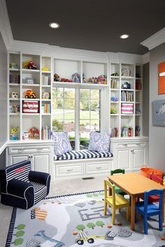 This playroom features a custom cabinet with open shelves, drawers, doors and a window seat - Barrington Homes Inc.