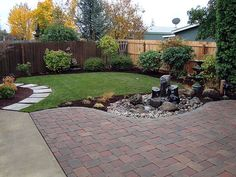 Backyard landscaping.  Great for small yard.  Like the fence color and small grass area.  Would do different trees along border and would make waterfall more modern, but very pretty overall.