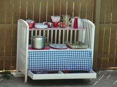 Outdoor entertaining is a breeze with this recycled baby crib as a serving table on wheels!