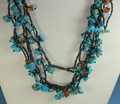 Seven strand necklace is made with polished turquoise nuggets with golden brown matrix, iridescent copper colored beads, small turquoise beads, and a few faceted topaz colored glass beads as accents. Necklace measures about 23 inches long. Fastens with a toggle type of fastener made out of beads. No signs of wear, and a beautiful necklace if you love turquoise! I am not an expert on Turquoise, but assume that these nuggets are stabilized turquoise. Please email with any questions, and thanks…