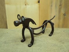 Weiner dog made out of Horseshoes and round bar steel, plus some nuts, washers and an old hammer head.