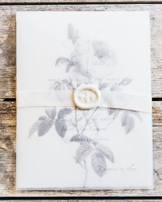 Vellum Layered Rose Invitation with Wax Seal Gray. White wedding stationery with a combination of handmade, hand moulded papers and vellum overlay on the deckled edged invitation. Invitation and response card were printed with a soft gray ink in a font suggestive of a carefully handwritten letter. Invitations were overlaid with thin vellum printed with drawings of gray roses in and wrapped in silk ribbon. White wax seals impressed with a bee stamp finished the suite. Gold calligraphy…