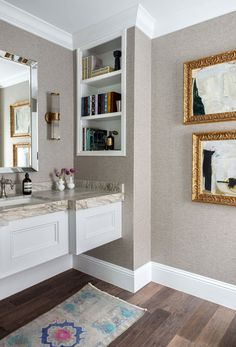 The powder bath is sheathed in a Phillip Jeffries wallpaper. The sink's fittings are from Kohler, the sconces are from Ralph Lauren Home, and the rug is vintage. #powderbathroom #powderroom #bathroom