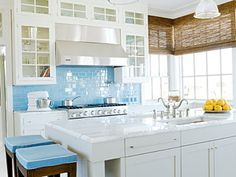 Bright coastal kitchen features crisp detailing. Clean white cabinets and a marble-topped island contrast with ocean-blue backsplash tiles and matching barstool cushions. Woven bamboo shades lend subtle texture and offer flexible sunlight control.
