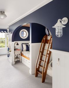 This boys' bedroom features cabin-style bunks and nautical blue on the walls.