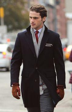 Stylish man on a cold day wearing gray silk scarf, charcoal top coat, gray suit, and contrasting red necktie.