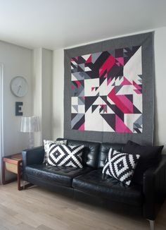 Decorating with quilts: this modern wall quilt is paired with black-and-white patchwork-style pillows