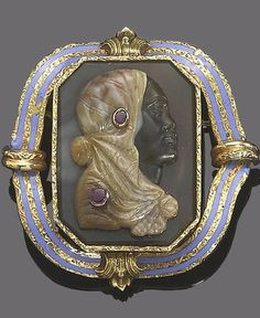 A mid 19th century cameo habillé brooch. The octagonal banded chalcedony plaque, set with a carved cameo of a lady facing right, with cabochon ruby highlights, within a textured border and an associated frame of light blue enamel and textured detail.