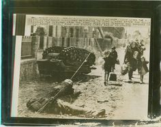 French civilians returning to Pont L'Abbe after the Allied pushed the Germans from the town, pass dead Germans and smashed German Equipment....