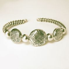 "I'd love to visit beautiful Bali someday. In the meantime, it can influence my jewelry creations.   This statement bracelet stars 3 large silver tone Bali style beads separated by 4 large sterling silver beads.   The band is wire wrapped, antiqued, tumbled and polished by hand.  It is flexible and can accommodate a wrist size of 6 ½"" to 9"" (16.51cm to 22.86cm)."