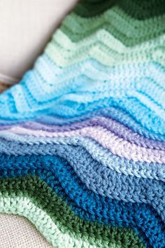 The shades of blue, green and purple in this crochet afghan resemble a vibrant sunset over a calm ocean.