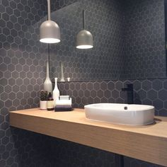 Dark grey tiles with contrasting lighter grey grout against light wood and white…