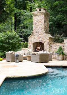 Outdoor fireplace placed on pool patio. Enchanting outdoor area with pool, patio and outdoor fireplace.