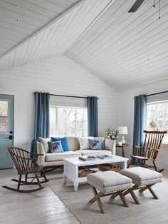 Amanda opted for white paint on the walls and ceiling & blue draperies that complement the sky outside. Light pine floors with a single coat of whitewash allow the wood's natural grain to show without taking away from the room's airy feel.