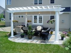 Small backyard patio design with white pergola and black rattan chair cushion sets