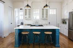 Welcoming blue and white bathroom boasts a blue shiplap center island seating wood and iron swivel counter stools in front of a white quartz countertop fitted with an integrated cooktop lit by two Murray Feiss Cadence Pendants.