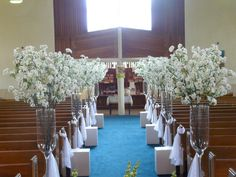 Everlasting cherry blossoms in glass vases for a dramatic church ceremony