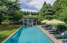 Adorable cedar shake poolhouse, navy chaises with white welting and buttons, and fringey lime green umbrellas, and hydrangeas galore by this Hamptons pool. Perfect casual prep-luxe.
