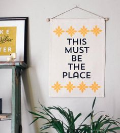 """This handmade canvas wall banner tells it like it is, talking about how sweet home can be. The line, """"This must be the place,"""" from the Talking Heads riff is printed in bold black type on cotton twill and framed with two rows of golden petals. Hang it anywhere you'd like a romantic sentiment."""