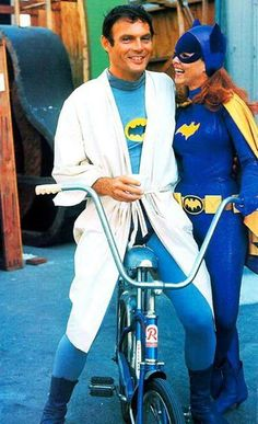 Adam West rides a bike. Yvonne Craig gets a grip. Batman and Batgirl, circa 1967.