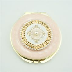 Mother of pearl compact mirror/Best vanity mirror This gold plated compact mirror is a perfect gift for lady. It is covered with pink enamel glaze and mounted with bling-bling crystals. There are two mirrors inside.