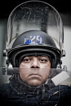 Toronto police officer in riot gear. Urban police in North America are now way beyond para-military with advanced military technology in weapons, battle gear, communications, intelligence, military command interface/coordination and more.
