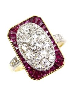 Early 20th century diamond and ruby oblong cluster ring, English c.1905, the central oval field pave set with diamonds, the largest to centre, to a canted rectangular frame set with calibre cut rubies, millegrain set in platinum and gold, two diamonds to each shoulder, gold shank