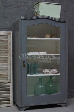 Vitrinekast 10199 - Brocante vitrinekast met een sierlijk golvende rand. De kast is grijs van kleur en heeft verstelbare planken. Leuke maat (161 cm) om bijvoorbeeld in de keuken te zetten!