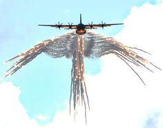 """A Lockheed Martin C-130 drops flares in an """"angel wing"""" pattern. The C-130 is the longest production aircraft in the world currently and is used world wide."""