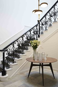 Wood table, glass vases, black staircase with detailed rails, and white stairs with grey carpet