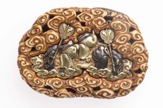Netsuke estilo Kagami-buta.  Medidas: 5.9 x 4.2 x 1.5 cm Materiales: oro y marfil (principalmente). Otros metales: plata, shakudo y shibuichi Museum of Fine Arts, Boston.