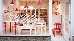Uma loja de doces com mesas e arrumação em branco e vermelho.