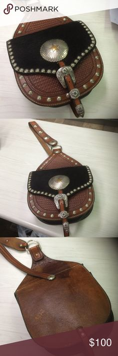 Vintage Silvertip Saddlebag Purse Vintage saddle bag-inspired purse is tipped with hand-worked silver and decorated a Star concho. The black flap of cow hide is a perfect complement for the chestnut leather and silver.  Hand-made by SilverTip out of New Mexico, who also did all the silver smithing, leather tooling and sewing. There is a bit of wear on the big sTar Cochin, it's a vintage piece and that's to be expected.  A darker spot on the leather on the back.  The inside is super clean…