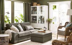 Un canapé trois places moderne en gris-vert avec repose-pieds dans un séjour aux murs verts.