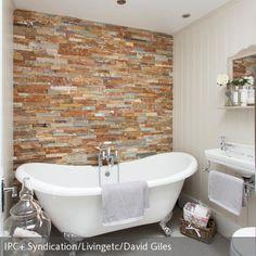 Diese freistehende Badewanne mit silberfarbene Löwenfüße steht im Kontrast zu der aufregenden Steinwand. Dieses Bad ist ein schönes Beispiel für ein…