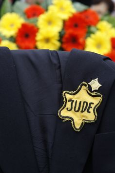 "A jacket belonging to Holocaust survivor, Mordechai Fuchs, with his Star of David. ""Jude"" meaning Jew."