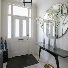 White hallway with contemporary console table and large round mirror