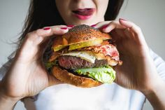Young lady holding huge burger - FoodiesFeed