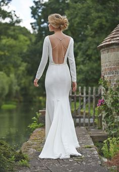 Clementine is a simple unstructured dress with solid long sleeves and a sculpted skirt and completely backless with elaborate back jewellery detail. Its made from an extremely high quality ivory crepe and a Swarovski jewel back accessory. #ivory #bridalgown #crepedress