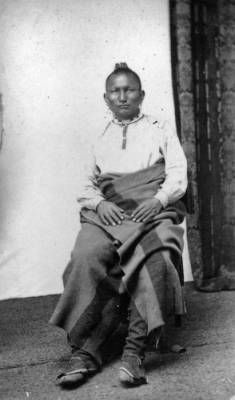 1875 Isaac H. Bonsall's studio portrait of an Iroquois man. He wears moccasins, leggings, a blanket, bead necklaces, and his hair in a Mohawk.