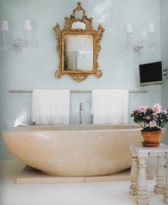 Vicente Wolf. Dreamy glass walls, Baccarat sconces, gilded mirror, and concrete tub.