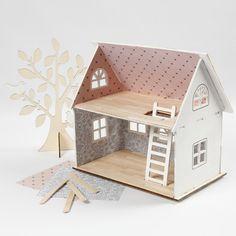 Kokoa vaaleapuinen nukkekoti. Maalaa julkisivu valkoiseksi ja kiinnitä kuviopaperia seiniin tapetiksi. Lisää jäätelötikkuja lattioihin ja bambulevyä kattotiiliksi.