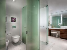 Green glass makes for sophisticated partition walls in the master bathroom, separating the toilet from the rest of the space.