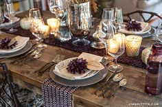 """Modern Thanksgiving Tablescape — from West Elm. Uses paper dahlias and gilded leaves to make a """"rustic glam"""" tablescape. The deep aubergine accents combined with metallics is gorgeous."""