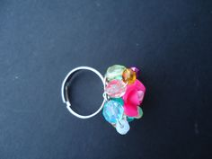 Pink clay flower and colorful glass beads of 2 different sizes on a ring base