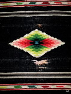 Well-used condition of this antique old Saltillo Mexico handwoven large wool rug blanket textile, found at an estate sale. We were told that the grandfather had collected items throughout the Southwest US in the 1930s. This heavy, soft and slightly furry wool blanket rug in beautiful colors measures a large 58 inches x 84 inches, plus the fringe (which appears to be all present). Gorgeous rich black background, with rows of bright stripes on the ends - some with arrows - and what I think…